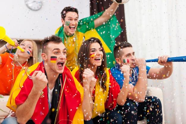 Eine gruppe multiethnischer menschen feiert den sieg der lieblingsfußballmannschaft