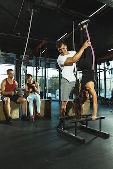 Eine gruppe muskulöser athleten, die im fitnessstudio trainieren