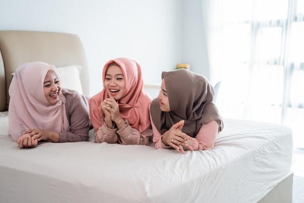 Eine gruppe muslimischer frauen, die auf dem bett liegen, genießen es, miteinander zu plaudern
