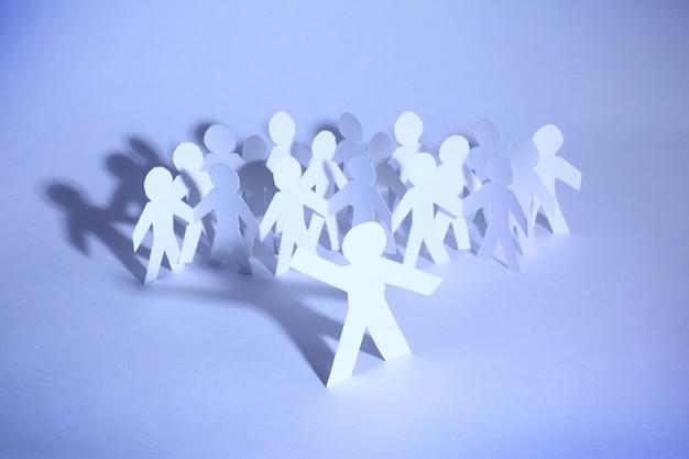 Eine gruppe papier menschen händchen haltend, die unterstützung, partnerschaft und zusammengehörigkeit der gemeinschaft anzeigen.