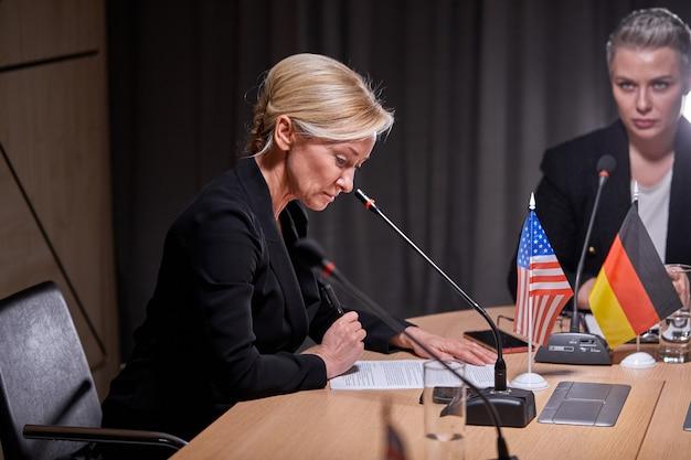 Eine gruppe politischer führer, die auf der pressekonferenz mit mikrofonen sitzen, sich unterhalten und ein treffen ohne bindungen abhalten, um ideen und themen auf der tagesordnung zu diskutieren. im modernen sitzungssaal