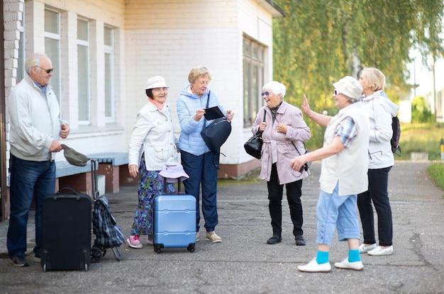 Eine gruppe positiver älterer älterer reisender, die auf den zug warten, bevor sie auf eine reise gehen