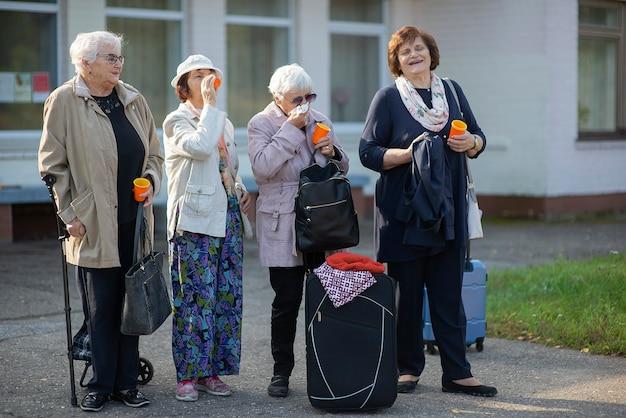Eine gruppe positiver älterer älterer reisenderinnen trinkt kaffee und kommuniziert, bevor sie auf eine reise gehen
