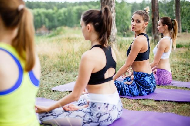 Eine gruppe schöne junge frauen, die zusammen yoga tun