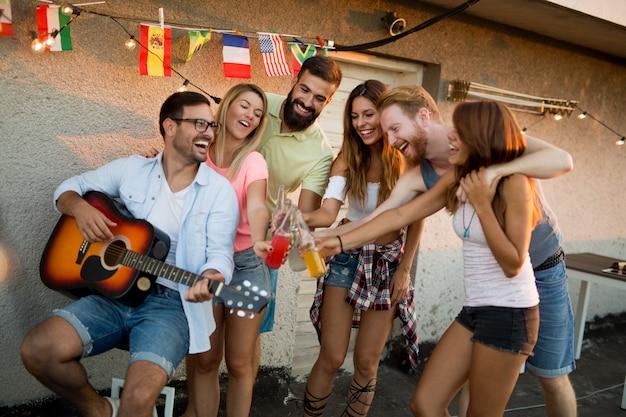 Eine gruppe schöner unbeschwerter freunde, die im sommer tanzen, hat spaß