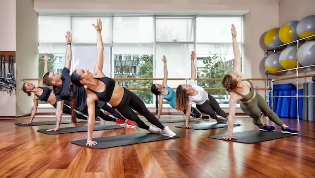 Eine gruppe sportlicher junger menschen in sportkleidung, in einem fitnessraum, die liegestütze oder planken im fitnessstudio tragen. gruppeneignungskonzept, gruppentraining, motivation