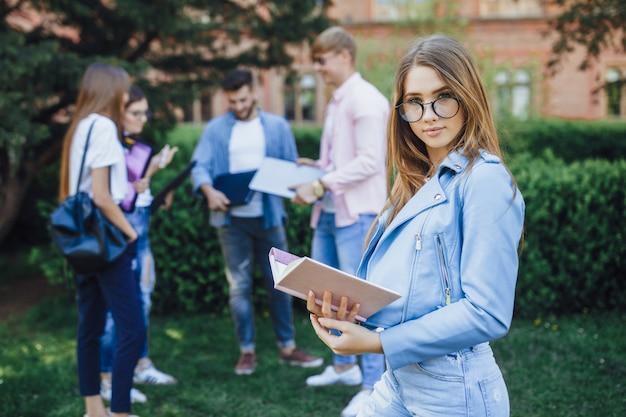 Eine gruppe studenten. porträt des jungen mädchens, das auf dem campus steht. halten sie ordner und rucksack in ihren händen.