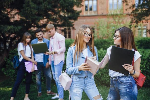 Eine gruppe studenten. zwei junge gute mädchen sprechen auf dem campus. halten sie ordner und rucksäcke in ihren händen