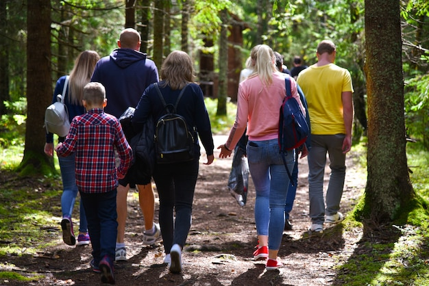 Eine gruppe touristen, die entlang einen waldweg gehen
