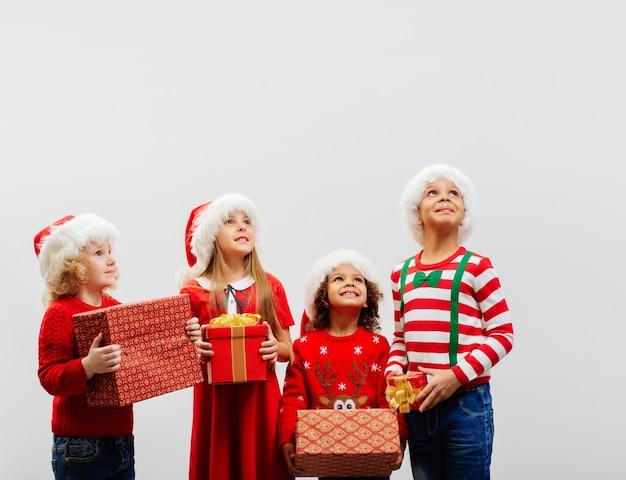 Eine gruppe verkleideter kinder mit weihnachtsgeschenken in der hand schaut interessiert auf
