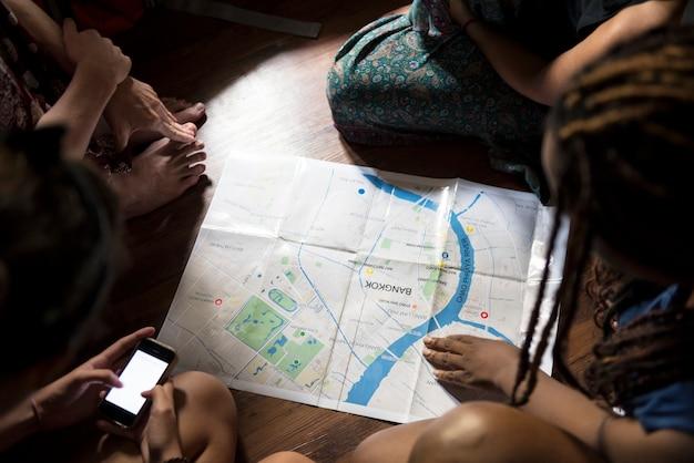Eine gruppe verschiedene touristen, die auf dem bretterboden plant und verwendet die karte sitzt