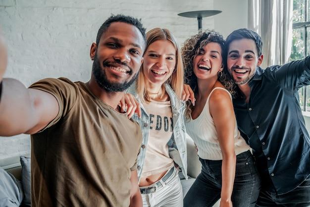 Eine gruppe verschiedener freunde, die spaß haben, während sie zusammen selfies machen. freunde-konzept.