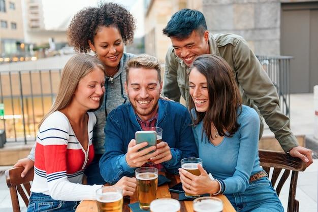 Eine gruppe verschiedener junger freunde versammelte sich an einem pub-tisch um ein smartphone, während sie lachend und scherzend ein bier genießen, während sie einen videoanruf tätigen