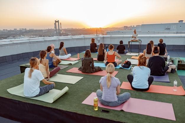 Eine gruppe verschiedener menschen praktiziert meditative yoga-übungen auf dem dach an einem wunderschönen sonnenuntergang am sommerabend