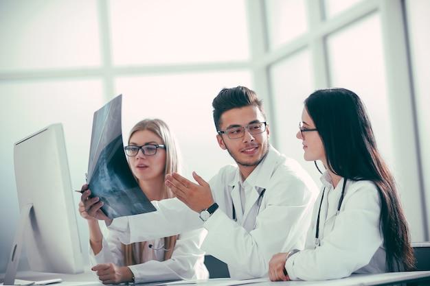 Eine gruppe von ärzten bespricht das röntgenbild des patienten mit kopienraum