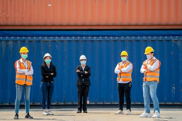 Eine gruppe von arbeitern trägt auf der baustelle schutzmasken und schutzhelme mit sozialer distanz