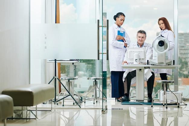 Eine gruppe von augenärzten versammelte sich am computer, um die testergebnisse des patienten zu besprechen und eine diagnose zu stellen
