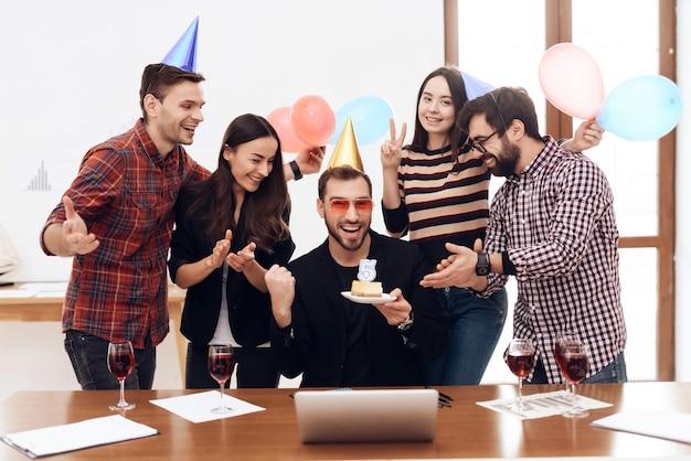 Eine gruppe von büromitarbeitern feiert tagesbegleitung.