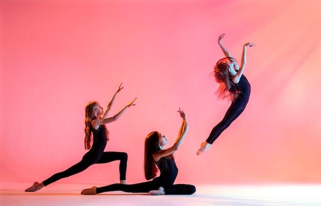 Eine gruppe von drei ballettmädchen mit langen fließenden haaren in schwarzen, eng anliegenden anzügen tanzt auf einem roten hintergrund