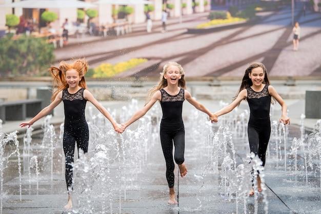 Eine gruppe von drei kleinen ballerinas in schwarzen, enganliegenden anzügen läuft an einem heißen tag zwischen plätschernden springbrunnen vor der kulisse einer stadtlandschaft auf den betrachter zu.