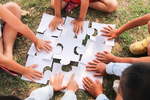 Eine gruppe von ethnisch unterschiedlichen schülern spielt zusammen puzzleteile auf dem spielplatz. teamwork, zusammenarbeit, lernen und bildungskonzept.