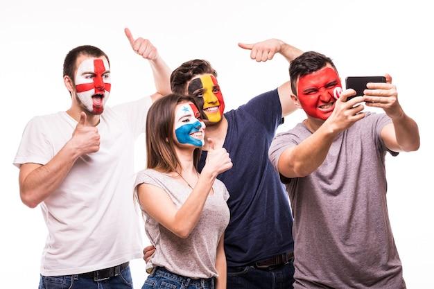 Eine gruppe von fans unterstützt ihre nationalmannschaften mit bemalten gesichtern. england, belgien, tunesien, panama fans nehmen selfie am telefon lokalisiert auf weißem hintergrund