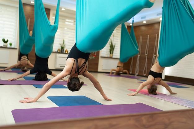 Eine gruppe von frauen hängt kopfüber in einer hängematte. fliegen yoga-kurs im fitnessstudio