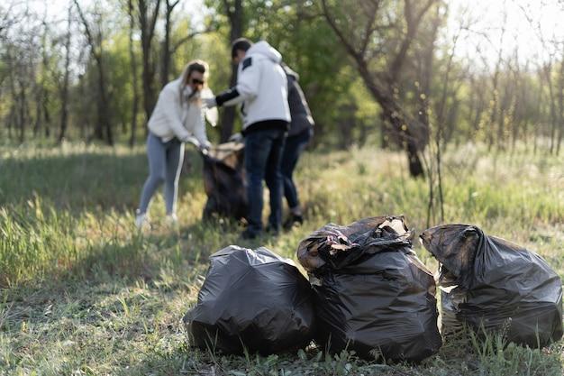 Eine gruppe von freiwilligen reinigt den park von trümmern. drei personen sammeln im frühjahr plastikmüll. konzept der umweltverschmutzung