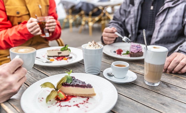 Eine gruppe von freunden auf einer restaurantterrasse im winter während der quarantäne covid-19. käsekuchen und heiße kaffees, die von freunden am caféhaustisch genossen werden.