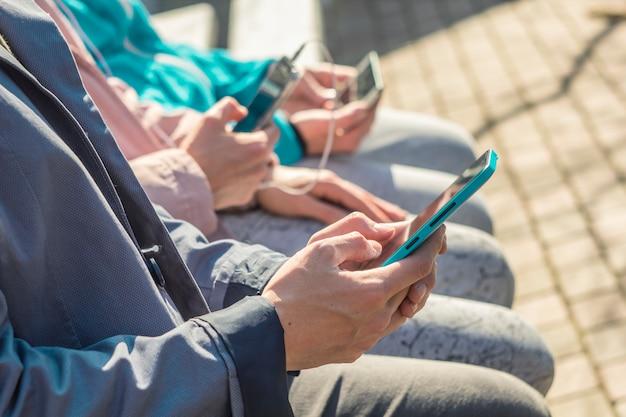 Eine gruppe von freunden benutzt telefone, um zu kommunizieren. gadgets in den händen von teenagern.
