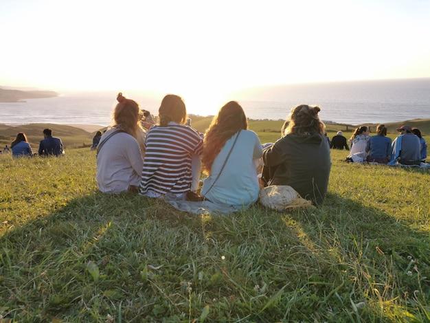 Eine gruppe von freunden, die den sonnenuntergang auf dem land genießen