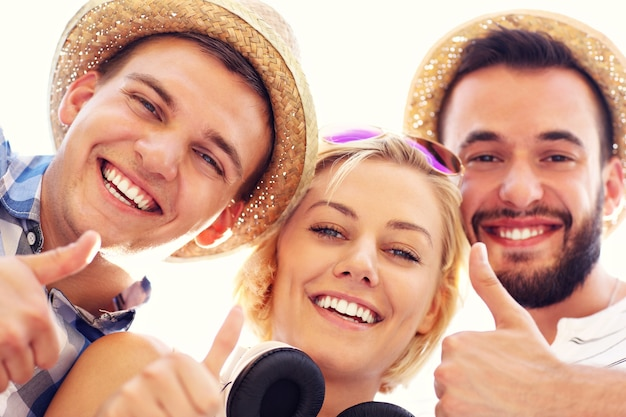 Eine gruppe von freunden, die der kamera gute zeichen zeigen