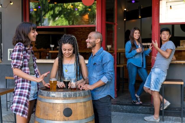 Eine gruppe von freunden, die draußen an einem brauereifass stehen, während sie getränke und spaß beim reden haben.