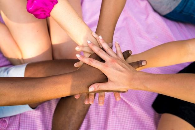 Eine gruppe von freunden, die ihre hände zusammenlegen