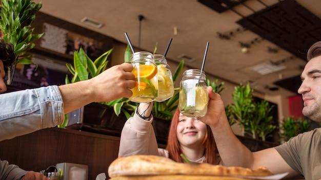 Eine gruppe von freunden, die sich in einer kneipe ausruhen. essen, trinken, essen auf dem tisch. freundschaft