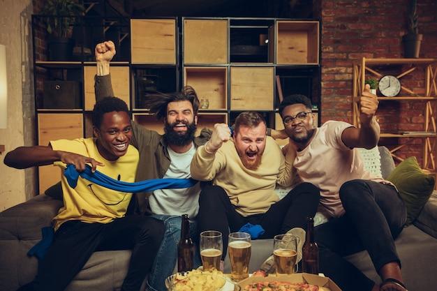 Eine gruppe von freunden, die tv-sport schauen, spielen emotionale fans zusammen, die dem lieblingsteam beim aufregenden spiel zujubeln
