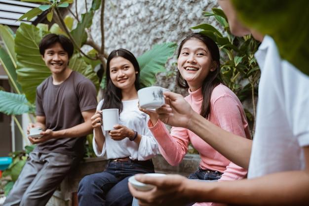 Eine gruppe von freunden entspannt sich und trinkt zusammen im garten