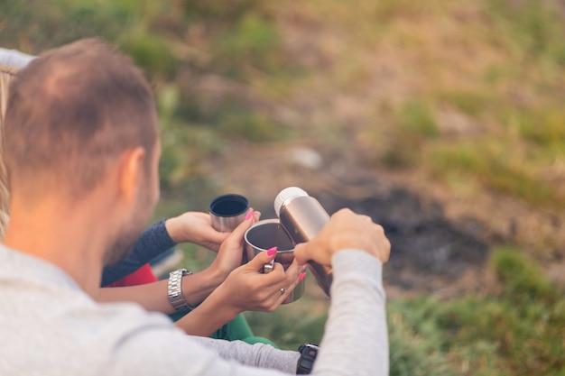 Eine gruppe von freunden genießt an einem kühlen abend am waldfeuer ein wärmendes getränk aus einer thermoskanne. fun time camping mit freunden