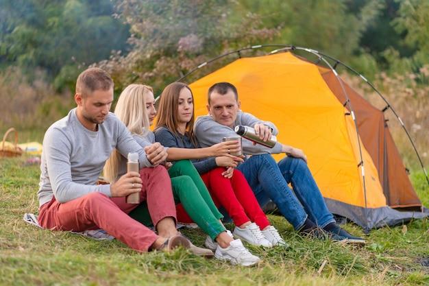 Eine gruppe von freunden genießt an einem kühlen abend am waldfeuer ein wärmendes getränk aus einer thermoskanne.