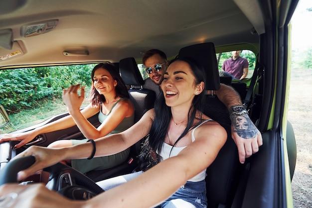 Eine gruppe von freunden hat eine reise. sitzt in einem modernen auto, unterhält sich und lächelt.