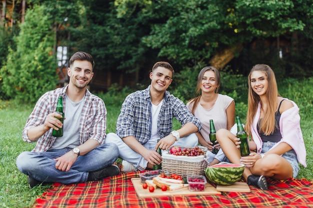 Eine gruppe von freunden hat spaß. fröhliche mädchen und männer verbringen das wochenende im freien beim picknick im park