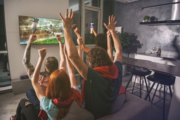 Eine gruppe von freunden sieht sich das spiel gemeinsam im fernsehen an und freut sich
