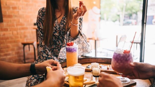 Eine gruppe von freunden sitzt im sommer auf der terrasse hinter einem holzfass mit cocktails und einem snack