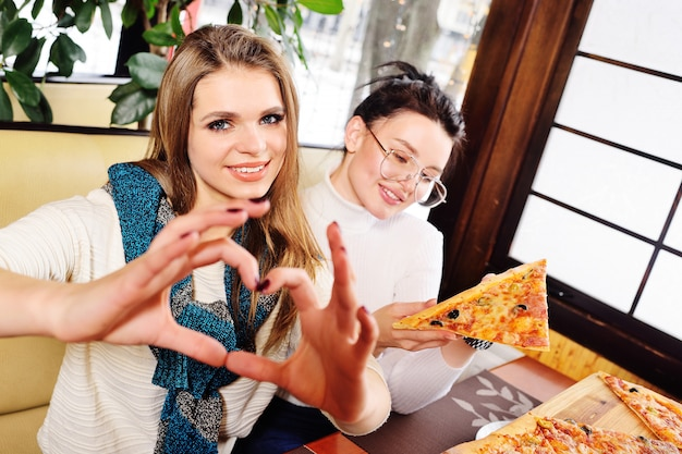 Eine gruppe von freunden spricht und lächelt in einem café und isst pizza.
