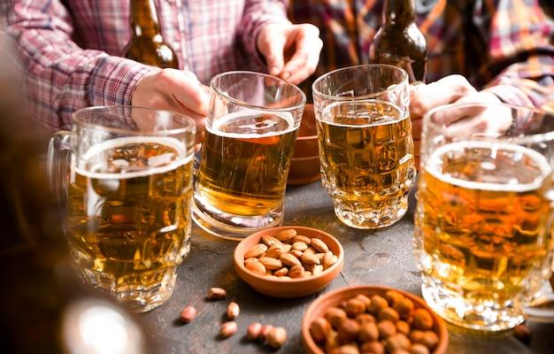 Eine gruppe von freunden trinkt bier aus bechern in einer bar am tisch.