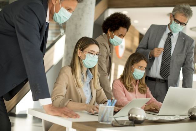 Eine gruppe von geschäftsleuten hat ein meeting und arbeitet im büro und trägt masken als schutz vor coronavirus