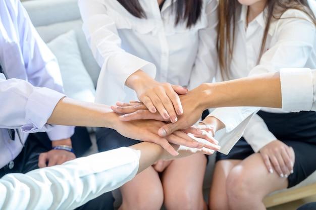 Eine gruppe von geschäftsleuten legt die hände zusammen, um die einheit im arbeitsteam zu gewährleisten