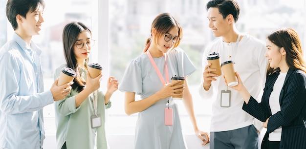 Eine gruppe von geschäftsleuten plaudert und trinkt während der pause kaffee