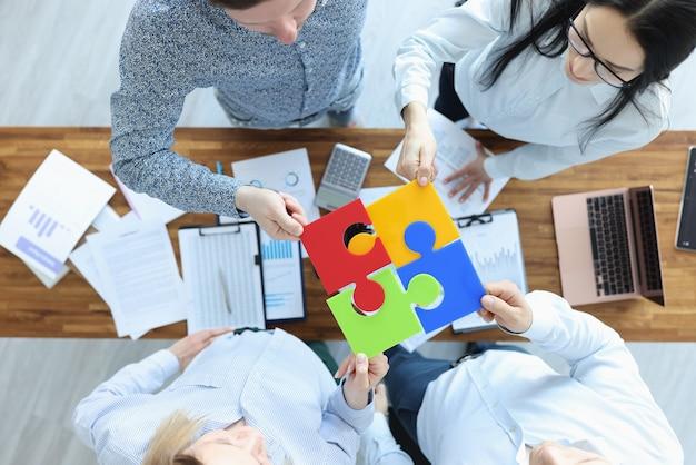 Eine gruppe von geschäftsleuten sitzt am tisch und stellt die bunte puzzle-draufsicht zusammen