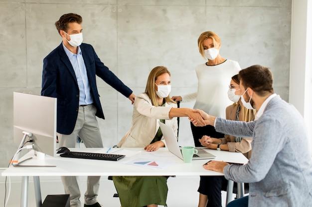 Eine gruppe von geschäftsleuten trifft sich und arbeitet im büro. sie tragen masken zum schutz vor dem koronavirus